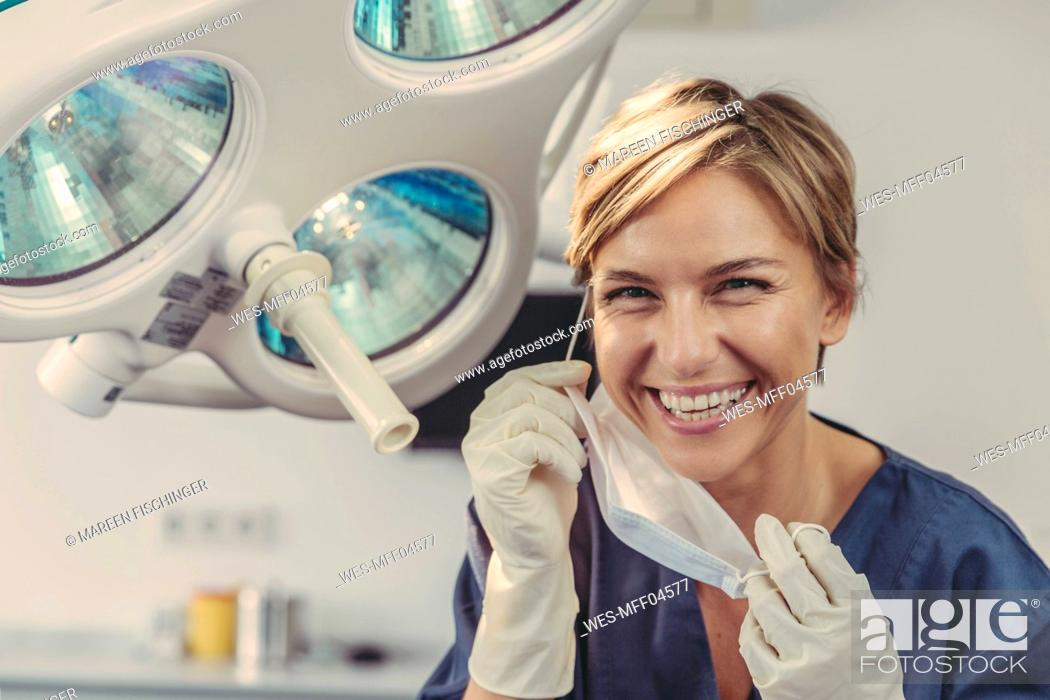 Stock Photo: Dental surgeon removing surgical mask, portrait.