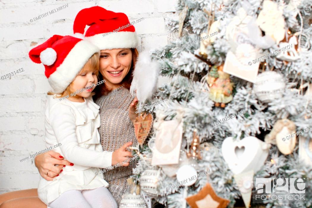 Stock Photo: The pretty girl with mum are decorating a Christmas tree in the house. Happy family.