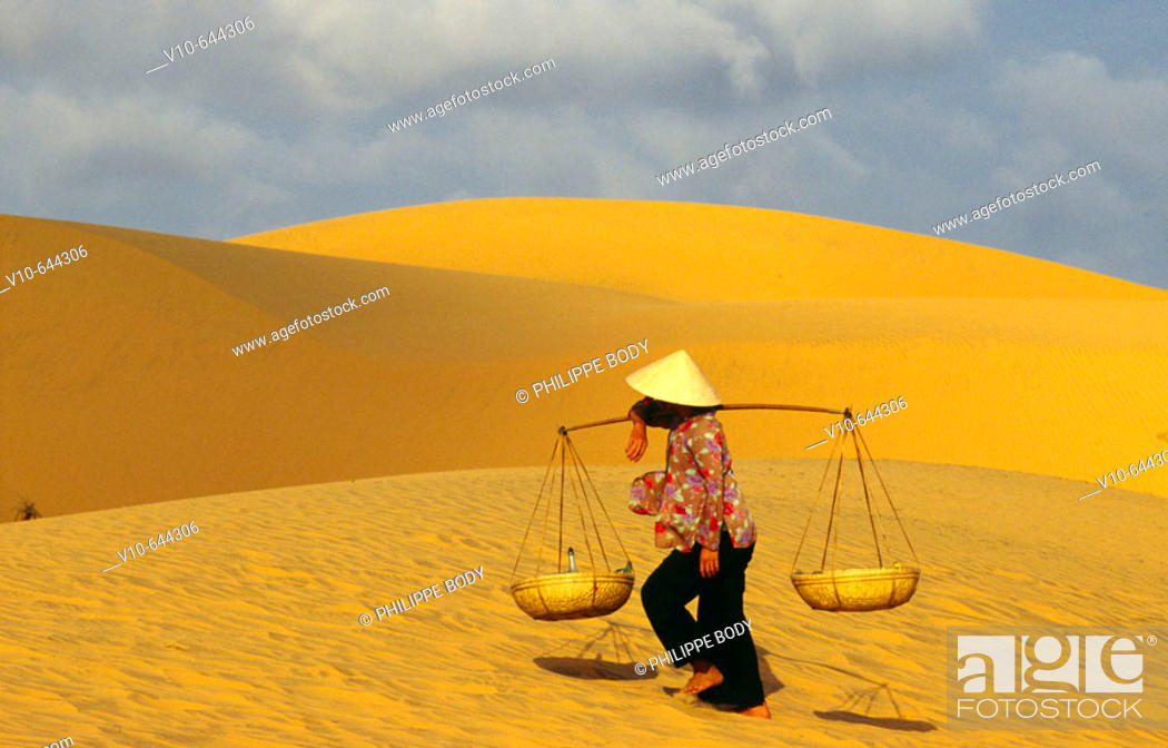 Stock Photo: Woman going to the market with her yoke, in the dunes of Mui Ne, Vietnam.