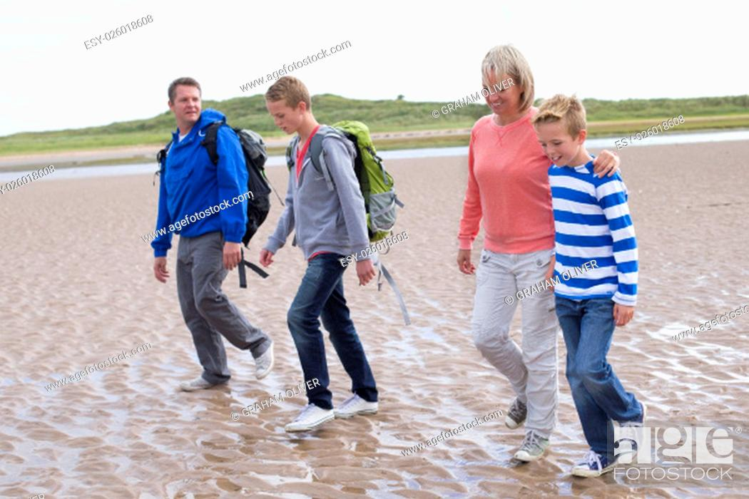 Stock Photo: Family of four walking across the beach. They are wearing warm casual clothing with backpacks and look very happy.