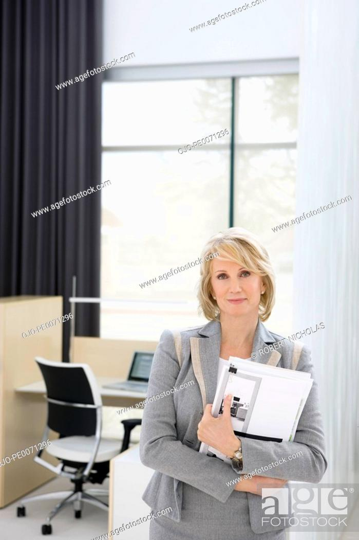 Stock Photo: Businesswoman holding paperwork in office.