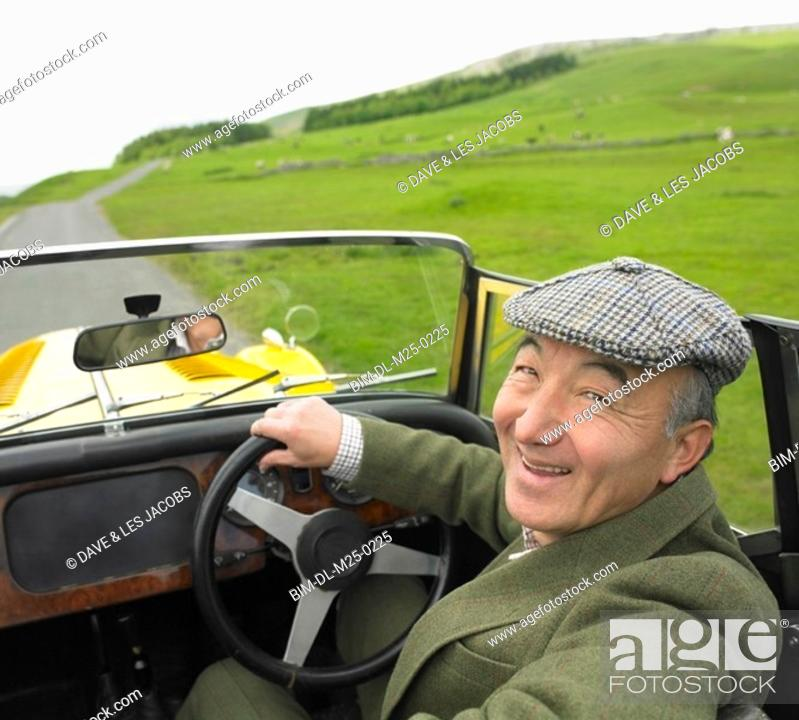 Stock Photo: Senior Asian man driving old fashioned sports car in countryside.