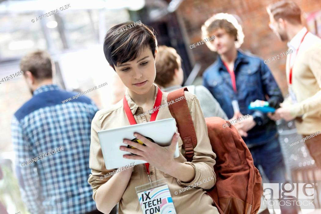 Stock Photo: Young woman using digital tablet at technology conference.