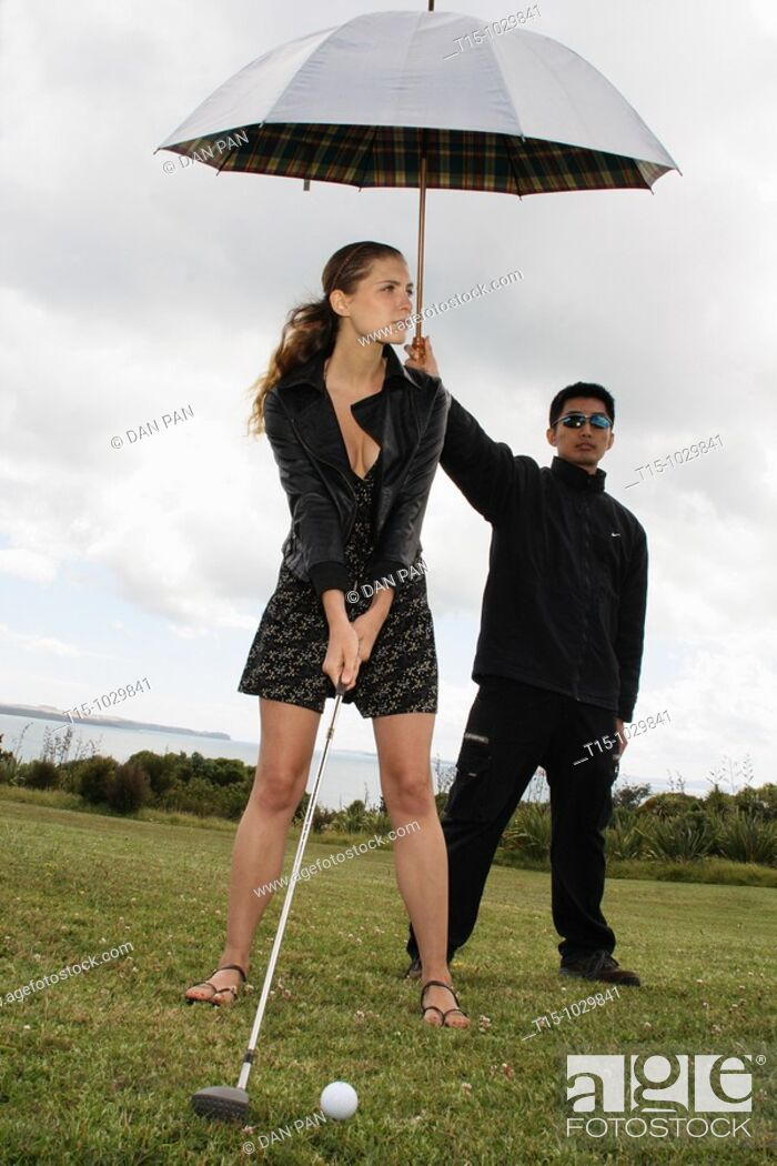 Stock Photo: woman golfing with a man holding umbrella for her.
