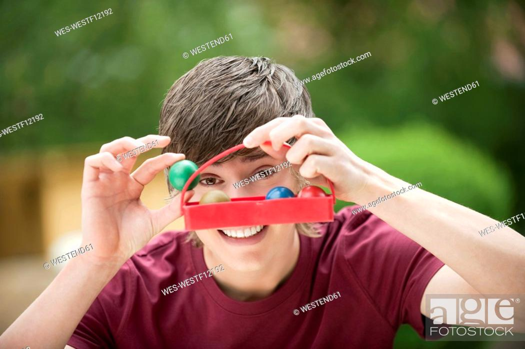 Stock Photo: Germany, Bavaria, Young man holding box with wooden balls, smiling, portrait.