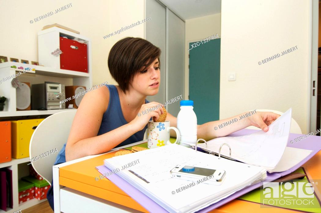 Stock Photo: Student working in her apartment with her breakfast.