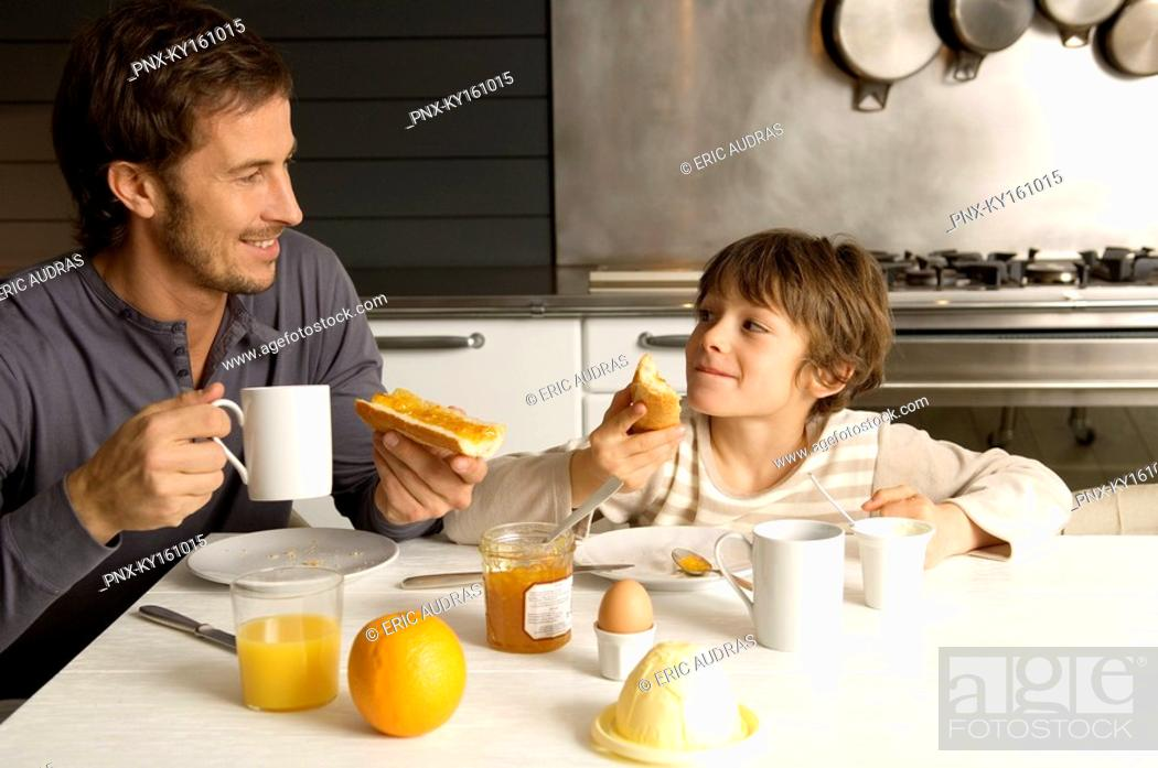 Stock Photo: Mid adult man having breakfast with his son.