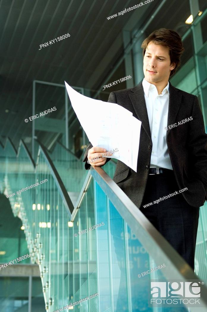 Stock Photo: Businessman looking at a blueprint.