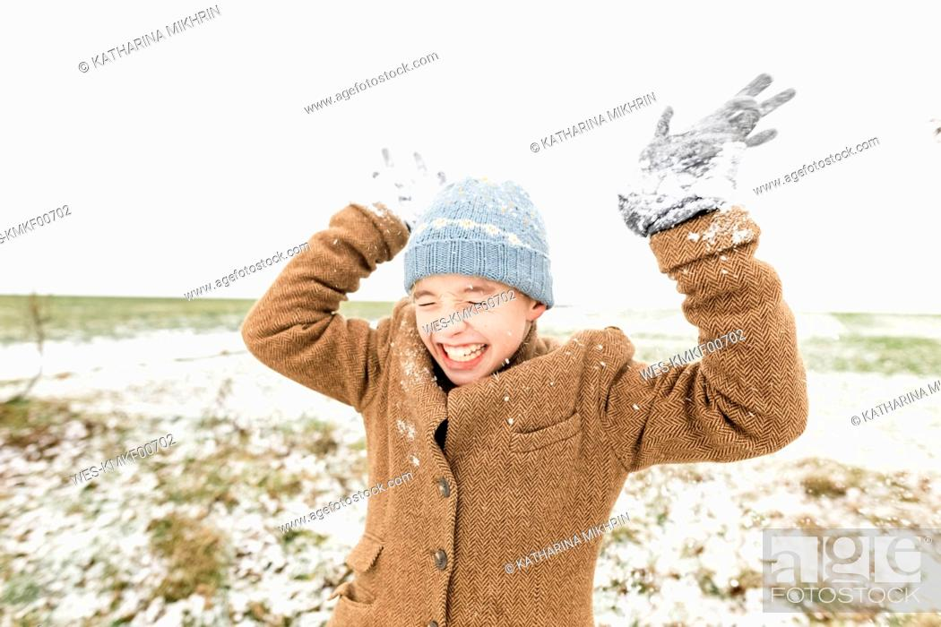 Stock Photo: Happy boy playing with snow in winter.