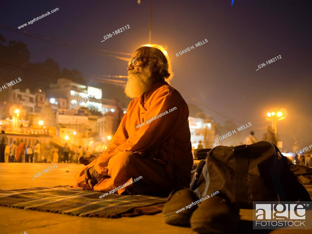 """Stock Photo: Pilgrim meditates during """"Arti"""" evening prayers on the ghats on the River Ganges in Haridwar in the state of Uttarakhand in northern India."""