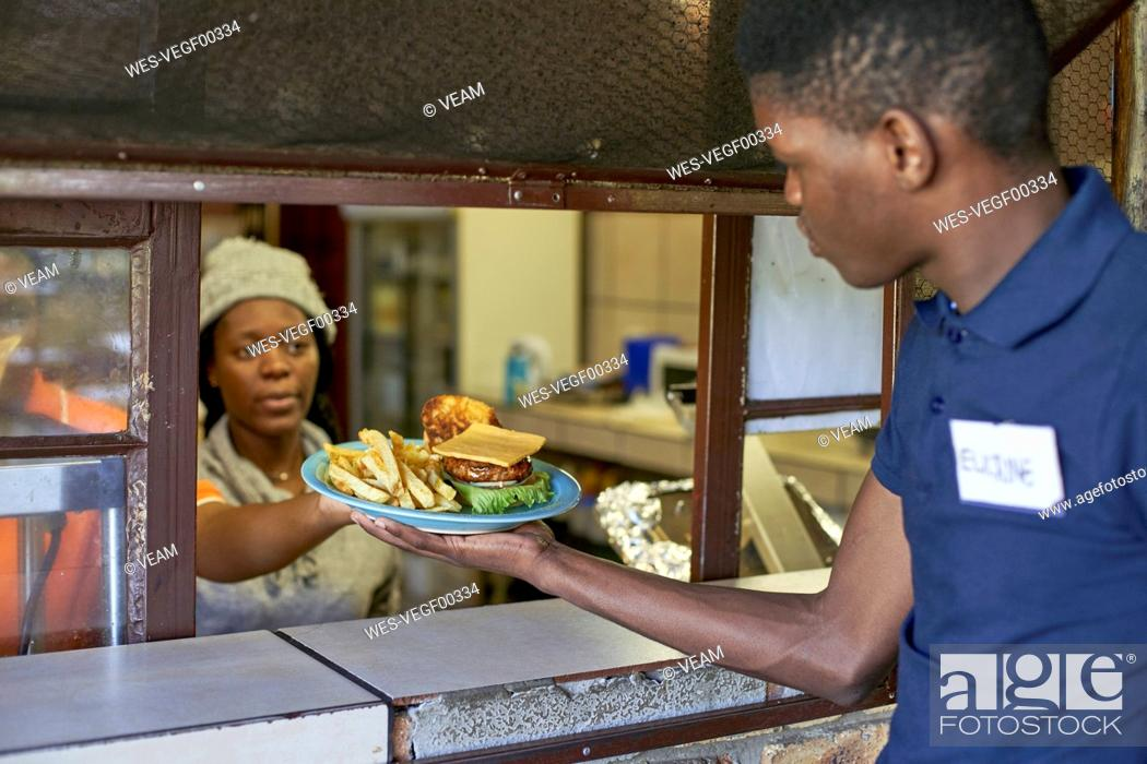Stock Photo: Young waiter taking delivered food from the restaurant kitchen, South Africa.