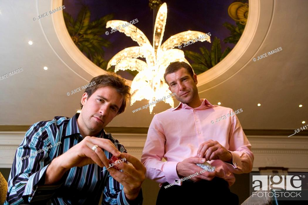 Stock Photo: Two young men with gambling chips, portrait, low angle view.