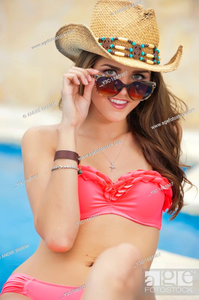 Stock Photo: Attractive young woman in red bikini with cowboy hat and sun glasses sitting at swimming pool.