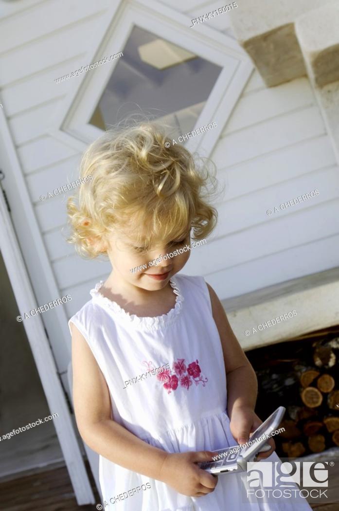 Stock Photo: Little girl holding mobile phone.