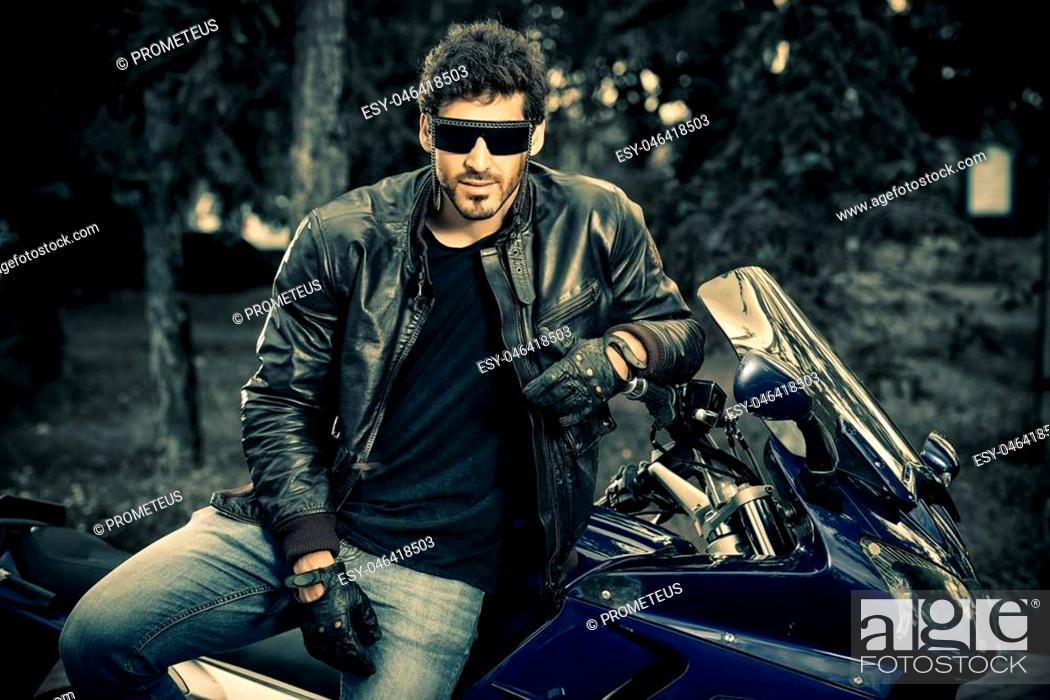 Imagen: Sexy biker man wearing jeans and leather jacket sitting relaxed on his motorcycle.