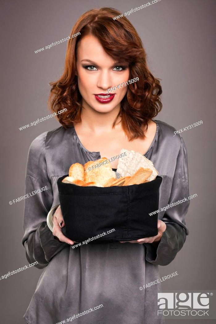 Stock Photo: Young woman holding basket of breads.