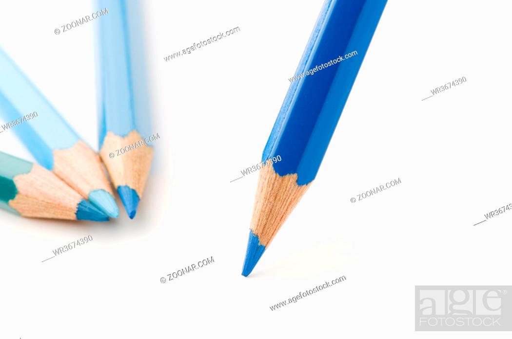 Stock Photo: Nahaufnahme blauer Buntstiftspitzen zueinander zeigend auf weißen Papier-Untergrund. Low angle closeup of blue crayon tips on white paper surface.