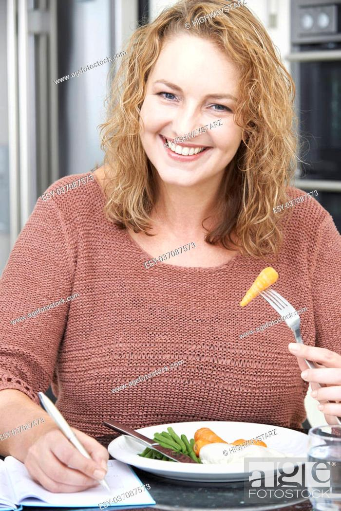 Stock Photo: Woman On Diet Writing Details In Food Journal.
