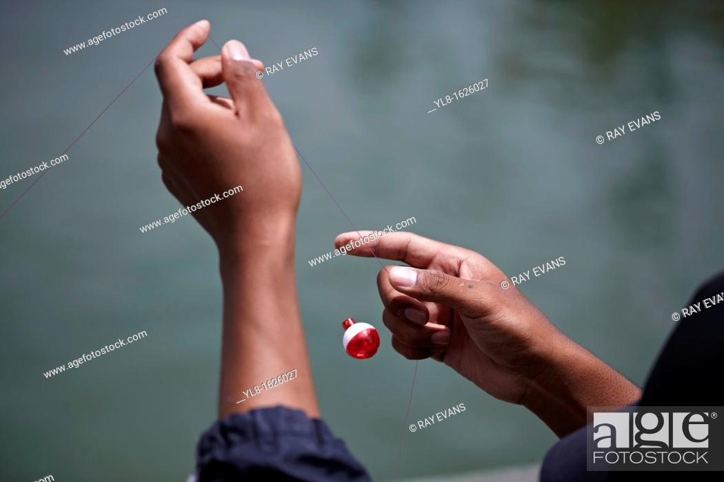Stock Photo: Close up of a fisherman tying a fishing float to line The float has slipped from his hands and is suspended in mid-air. Thailand S.E. Asia.
