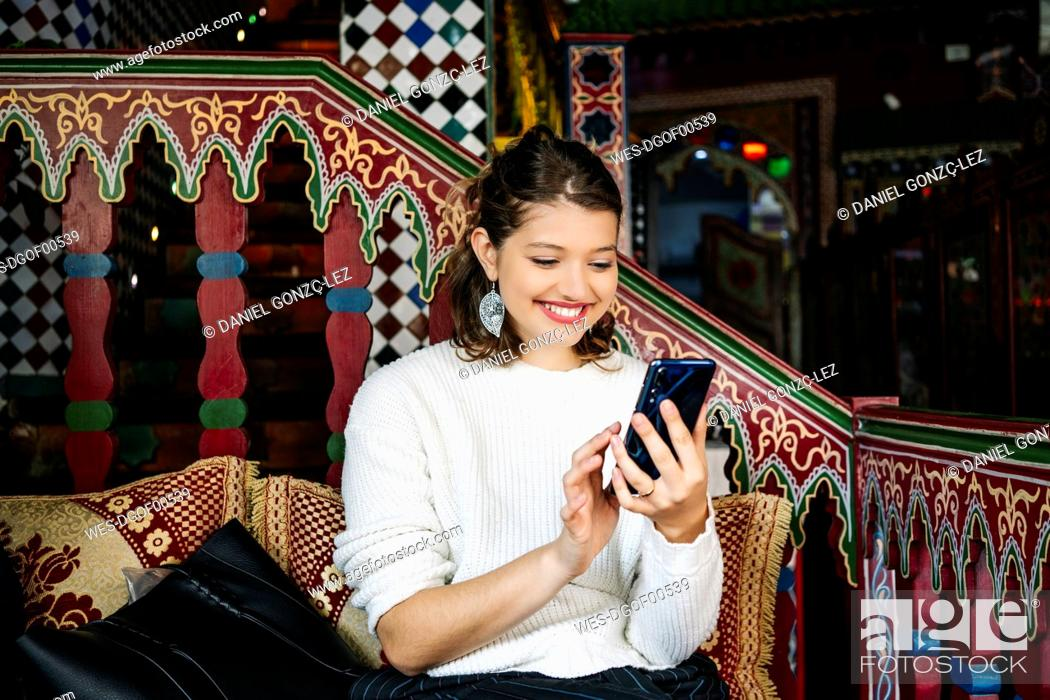 Stock Photo: Portrait of happy young woman in a tea shop using smartphone.