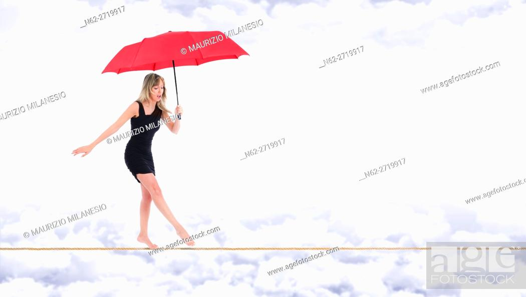 Stock Photo: Barefoot woman, walking very focused on a rope with a red umbrella in hand, on the bottom white clouds in a blue sky.