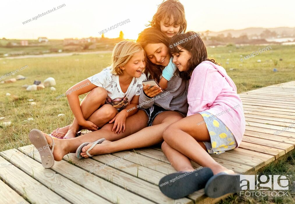 Stock Photo: Four girls sitting together on boardwalk looking at cell phone.