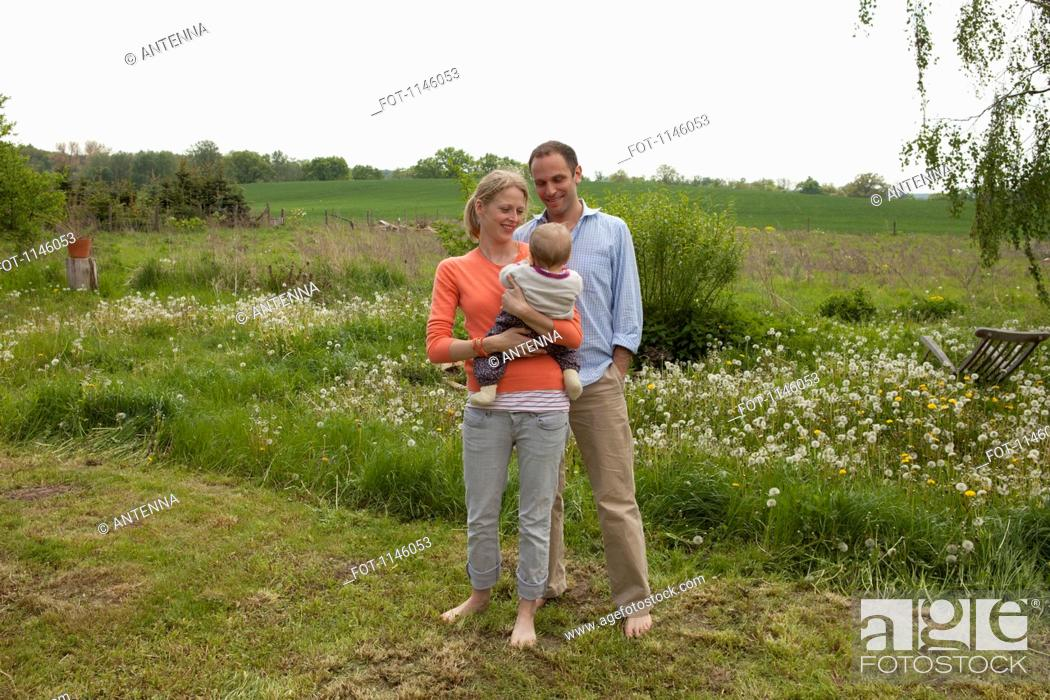 Stock Photo: A man and a woman holding a baby standing in their backyard.