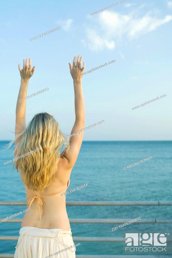 Stock Photo: Woman standing at railing by the sea, arms raised, rear view.
