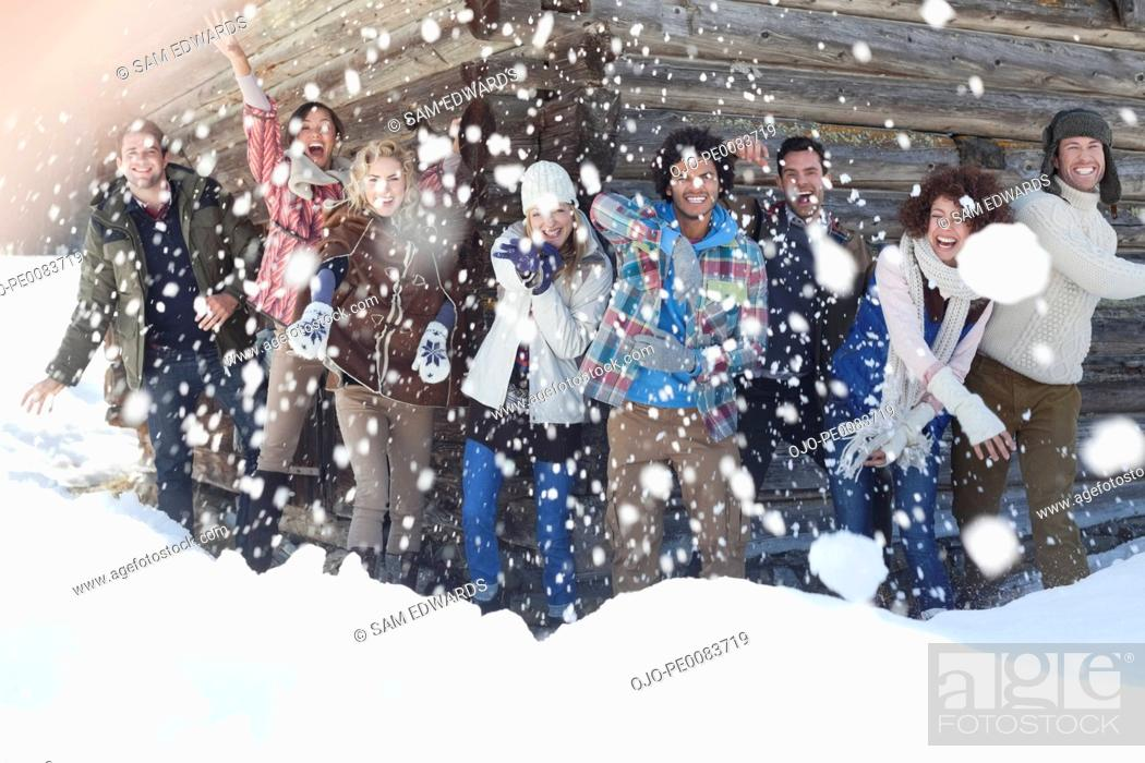 Stock Photo: Portrait of smiling friends throwing snowballs in front of cabin.