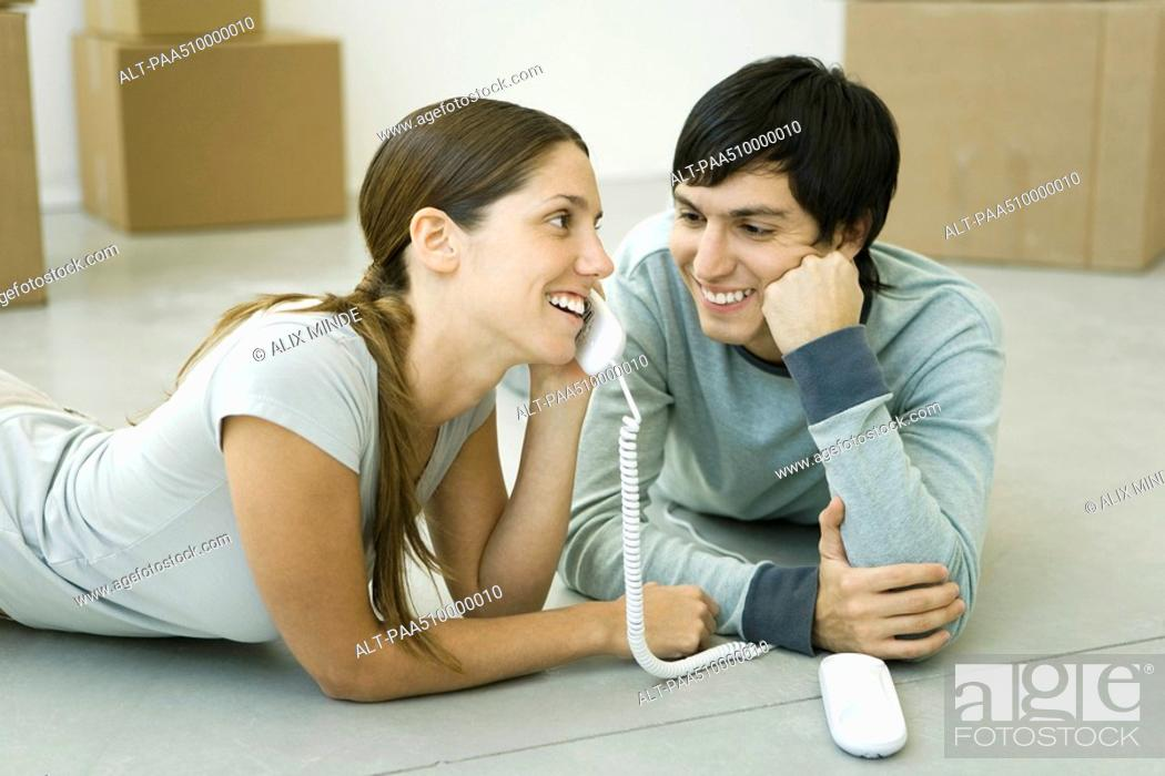 Stock Photo: Couple lying on the floor, woman talking on landline phone, boxes in background.
