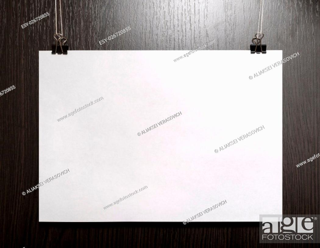 Stock Photo: Blank horizontal paper poster hanging on dark wooden background. Front view.