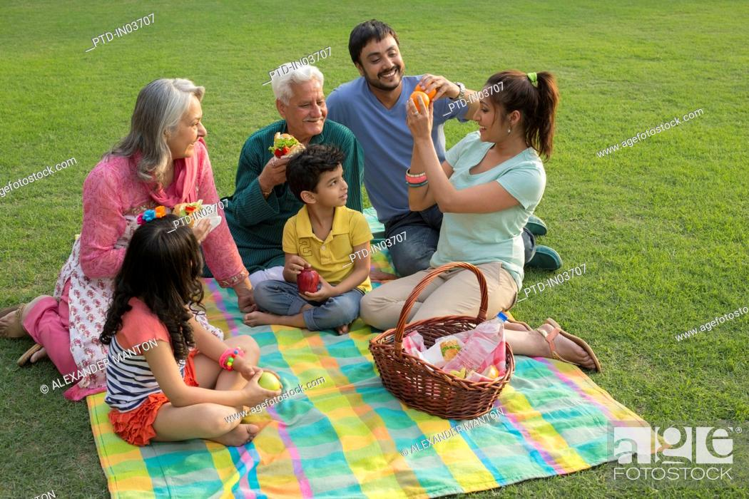 Stock Photo: Mother handing out food at family picnic with children (4-5).