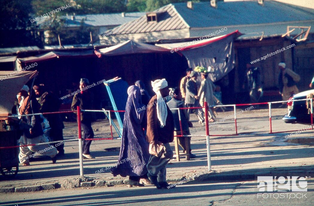 Imagen: Street scene with many people in Kabul, Afghanistan, November, 1975. A man and a veiled woman in a traditional Afghan burka walk together in center frame.