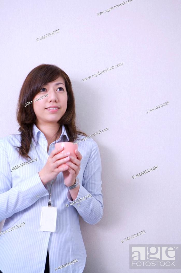 Stock Photo: Young woman holding a cup and looking up with smile.