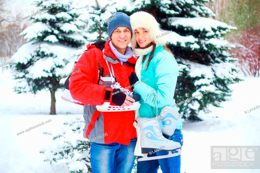 Stock Photo: happy young couple going ice-skating outdoor in wintertime.