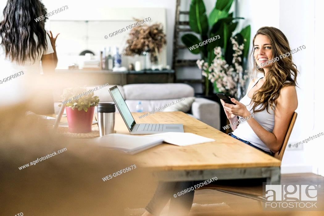 Stock Photo: Smiling woman with cell phone at table at home.