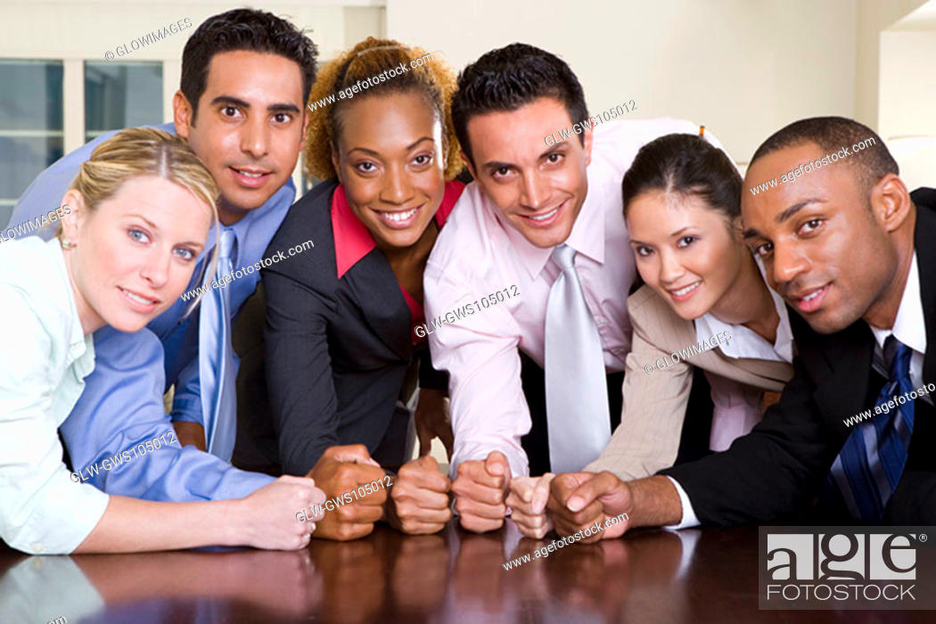 Stock Photo: Portrait of a group of business executives pounding their fists on a conference table.