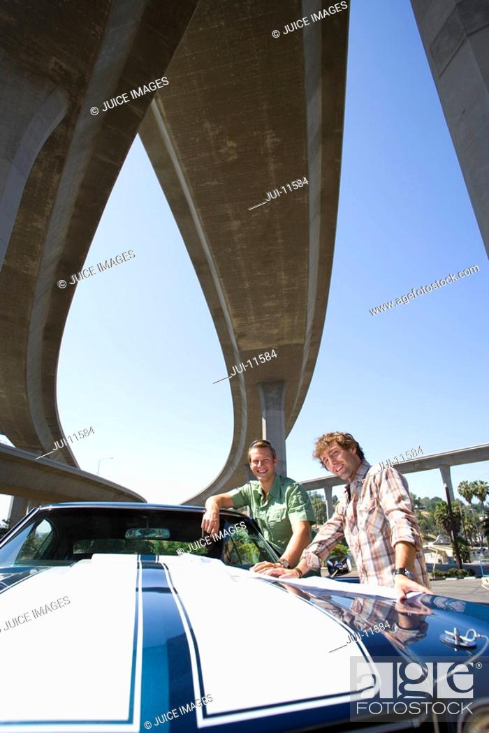 Stock Photo: Two young men by car beneath overpass, smiling, portrait, low angle view.
