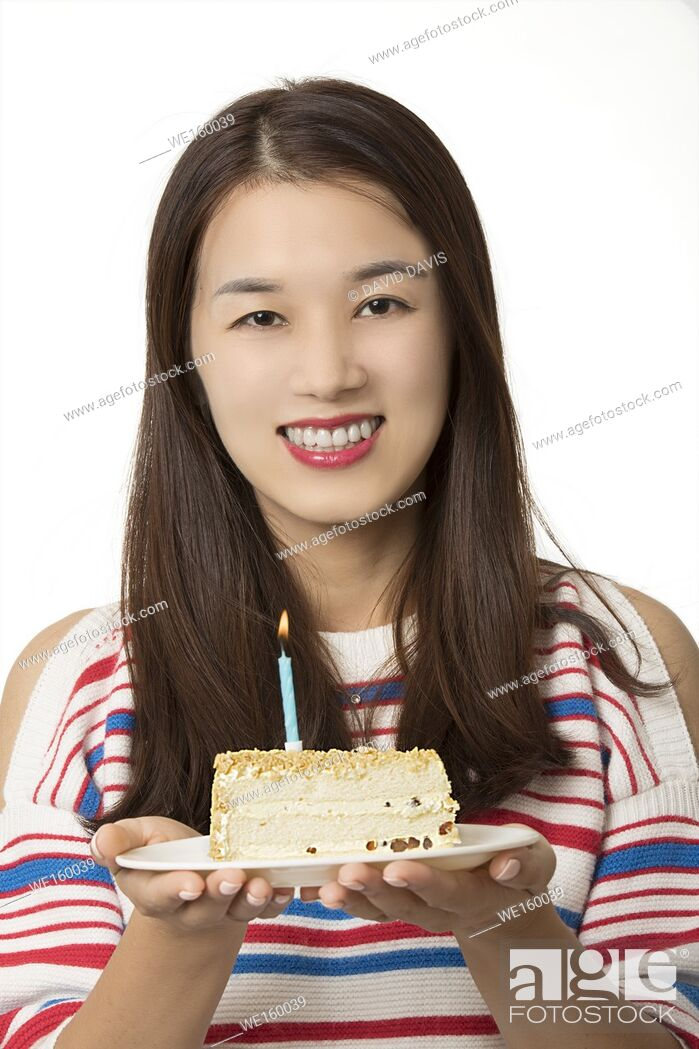 Stock Photo: Beautiful Asian woman holding a birthday cake isolated on a white background.