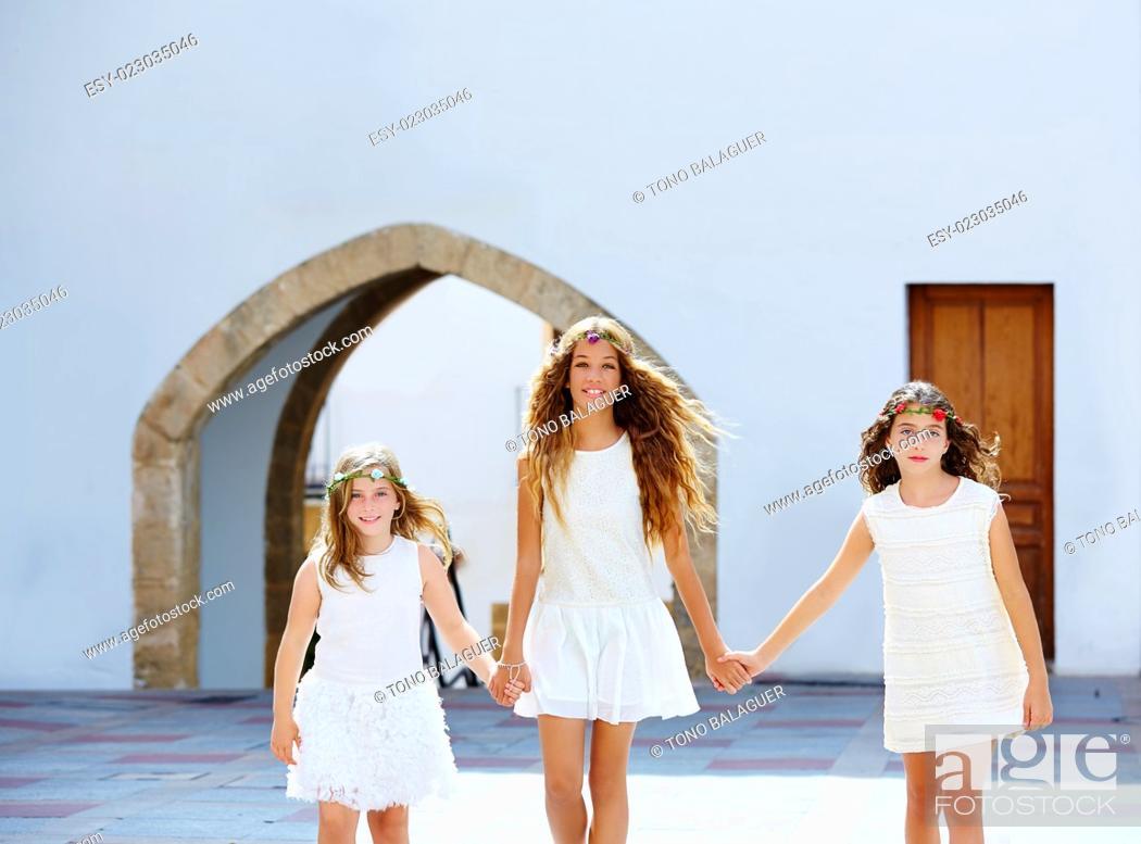 Stock Photo: Kid girls walking hand in hand at white Mediterranean village of Spain.