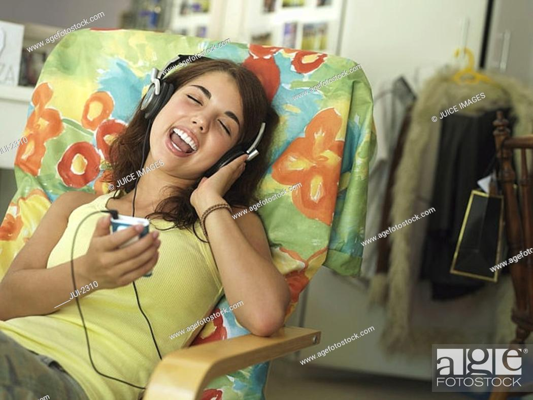 Stock Photo: Teenage girl 15-17 sitting in armchair at home, listening to MP3 player, singing, eyes closed.