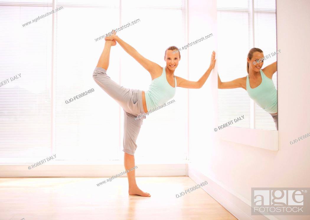 Stock Photo: Portrait of smiling woman stretching in fitness studio.