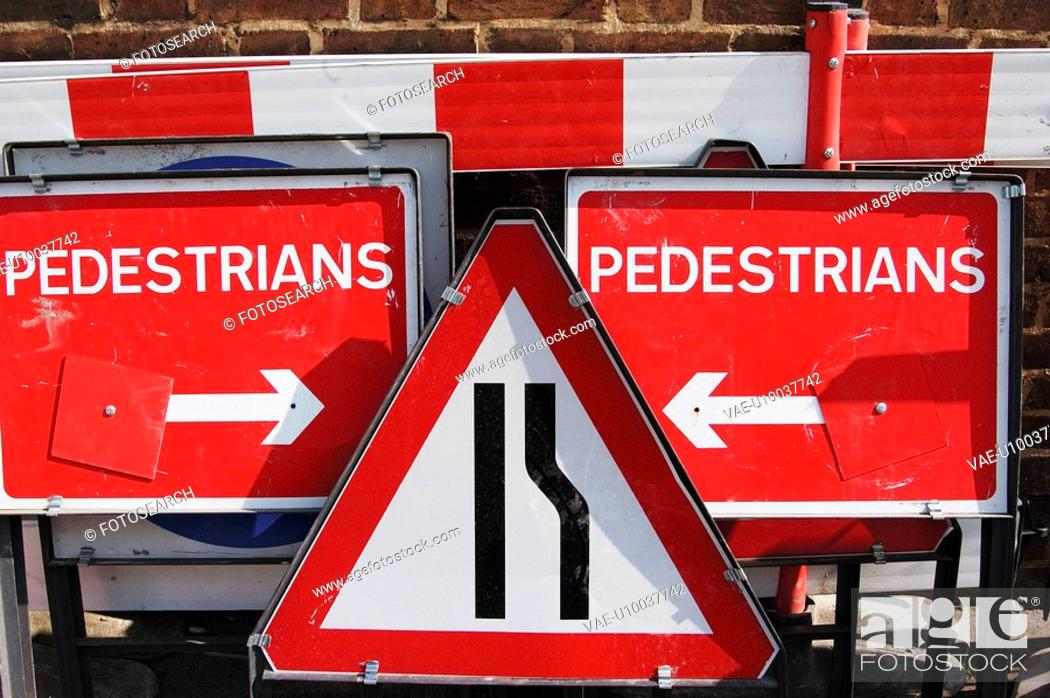 Stock Photo: Traffic roadwork signs stacked together on a pavement.