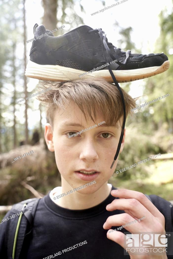 Stock Photo: Young boy in forest with sneaker on his head. Bad Tölz, Upper bavaria, Germany.