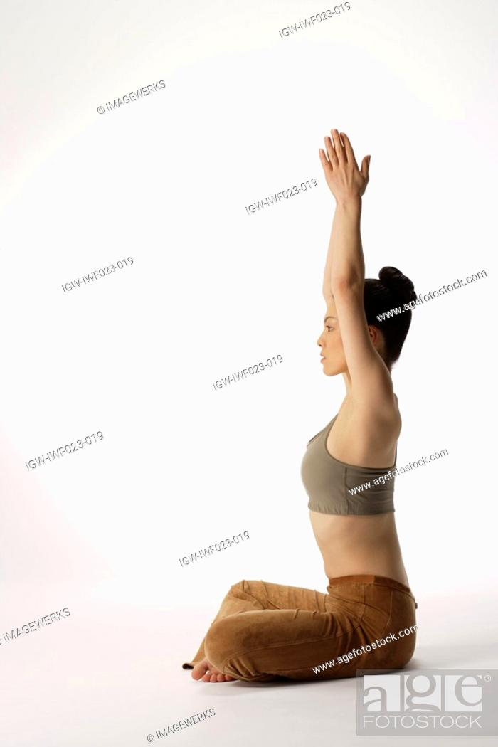 Stock Photo: Side view of a young woman meditating in lotus position.