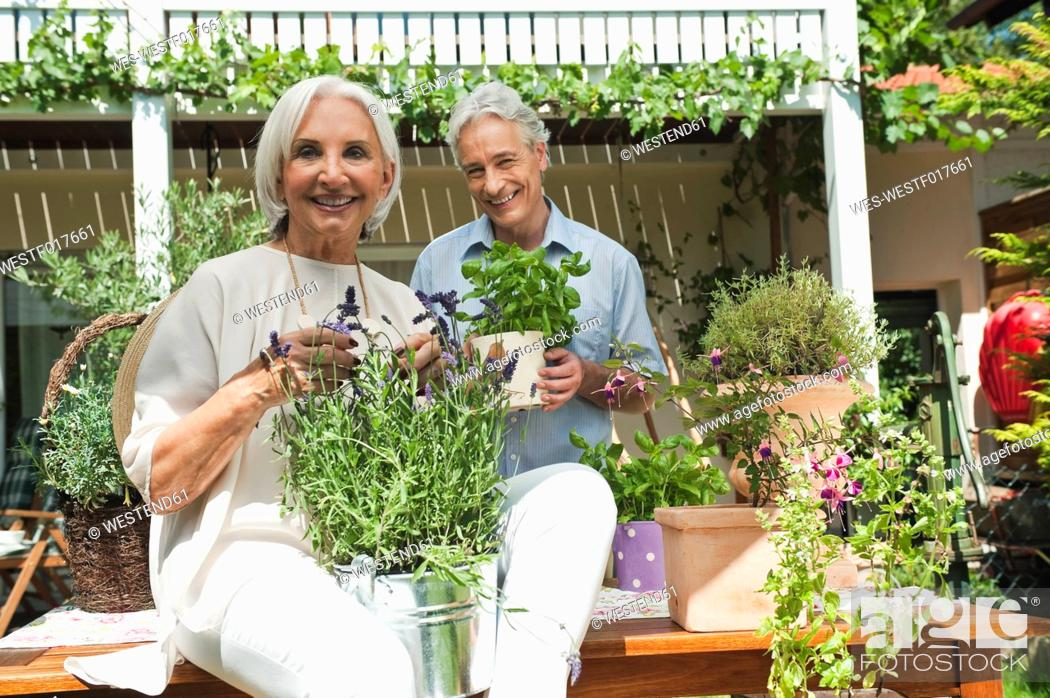 Imagen: Germany, Bavaria, Man and woman with potted plants.
