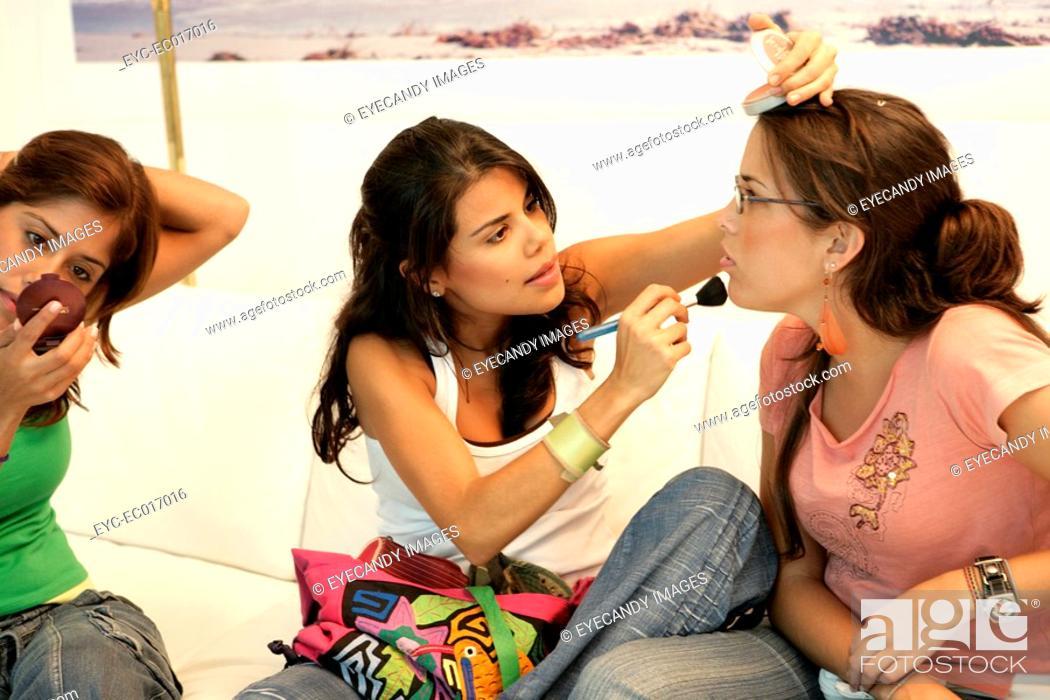 Stock Photo: View of three women applying cosmetics.