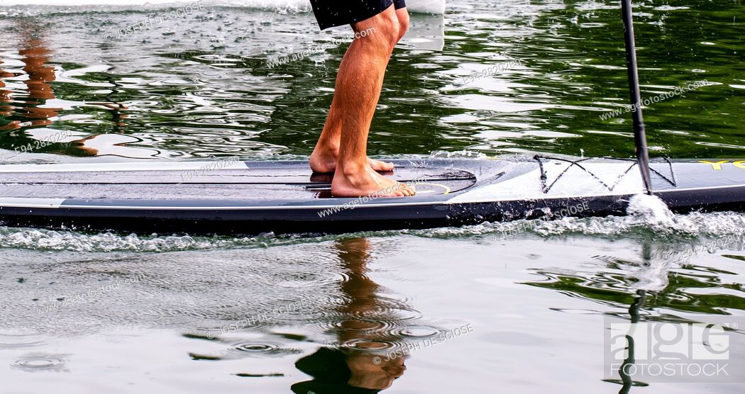 Stock Photo: Partial view of a young man's legs standing on a paddle board on a lake.
