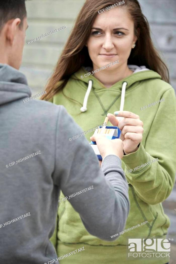 8f2d4e528 Boy Offering Teenage Girl Cigarette Outdoors