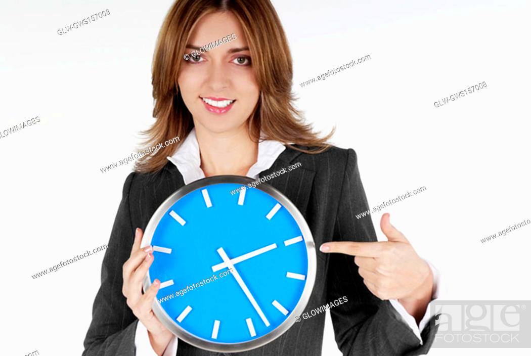 Stock Photo: Portrait of a businesswoman pointing at a clock and smiling.